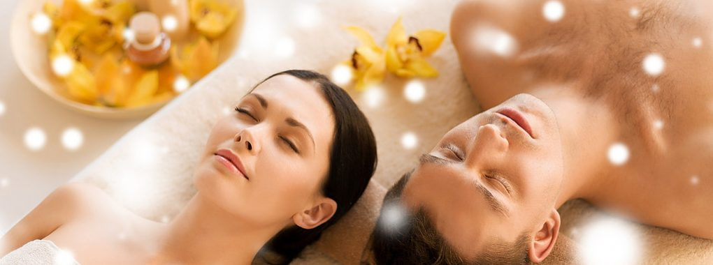 health and beauty concept — couple in spa salon lying on the mas